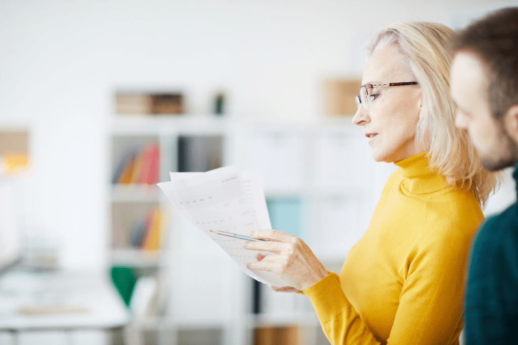 Side view portrait of successful mature businesswoman reading documents in office, copy space