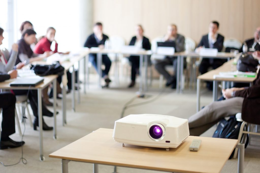 Projector on table; in the background are employees attending a training