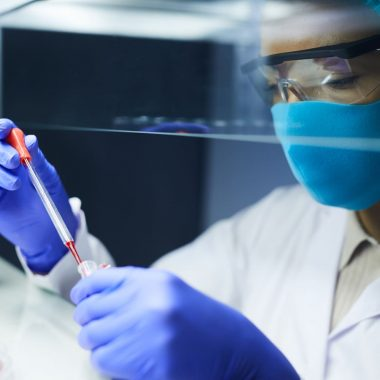 Side view portrait of female scientist wearing mask and protective gear dropping blood samples in test tubes while working on research in laboratory, copy space